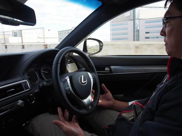 """トヨタ自動車の実験車で高速道路で自動運転中にハンドルから手を離すドライバー。「実用化には課題がある」(担当者)というが、高速道路に""""両手放し""""の運転手があふれる未来は近いと実感した、と助手席に同乗した産経新聞の記者は話す。"""