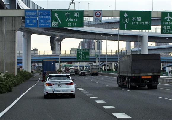 自動運転で高速道路の出口へ向かうトヨタ自動車の実験車(左)=6日、東京都江東区の有明インターチェンジ周辺(会田聡撮影)