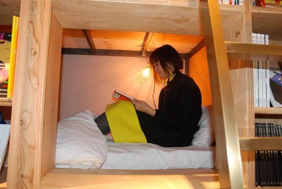 本棚に埋め込まれた「BOOK SHELF」タイプのベッド。棚の裏側にベッドスペースが隣接(写真はスタッフ)。カーテンを開けていると丸見えに思えるが、かがんだり、のぞきこまないと目線が合うことはない