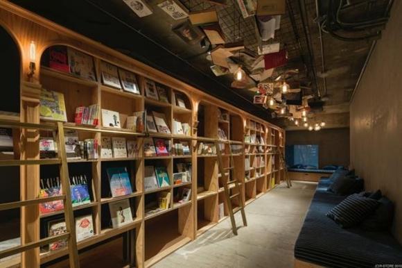 広さは約140平方メートルとコンパクトな空間。壁面を本棚が覆う。本棚のまわりは共有のラウンジスペースとなっており、デイユースの場合、ベッドは使用できず、このスペースを利用できる。天井には本がインテリアとして飾られている