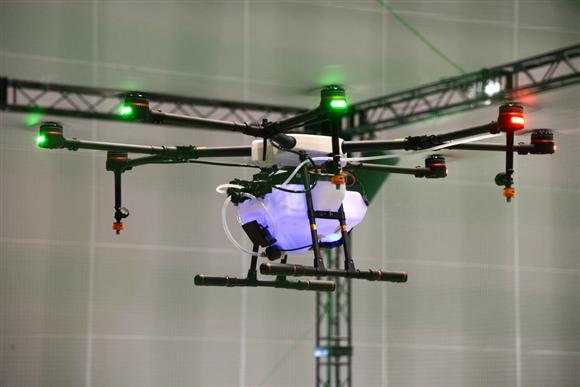 DJIの農薬散布ドローン「AGRAS MG-1」の飛行デモンストレーション 10リットルのタンクを搭載し青いランプで液体の残量を確認できる