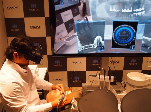 ソフトバンク子会社などが開発した、MR(複合現実)を使った歯科医療支援システムのデモ。後ろの画面には、歯科医役の人がゴーグル型端末を通して見ている光景が映し出されている=21日、東京都江東区