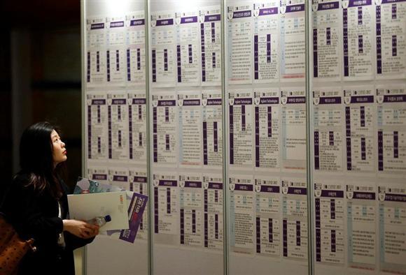 ソウルで4月に開かれた就職フェアで、求人情報に見入る女性(ロイター)