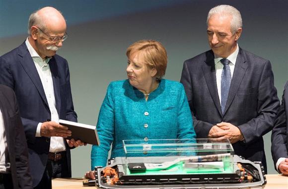 新工場の式典に参加したダイムラーのツェッチェ社長(左)と、ドイツのメルケル首相(中央)ら。このあと、ディーゼル車に不正な排ガス規制逃れの疑惑が浮上した=今年5月、ドイツ・カーメンツ(ロイター)
