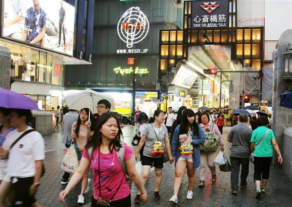 訪日外国人客らでにぎわう大阪・ミナミの戎橋付近。韓国国民に8人に1人が日本を訪れるという=今年6月