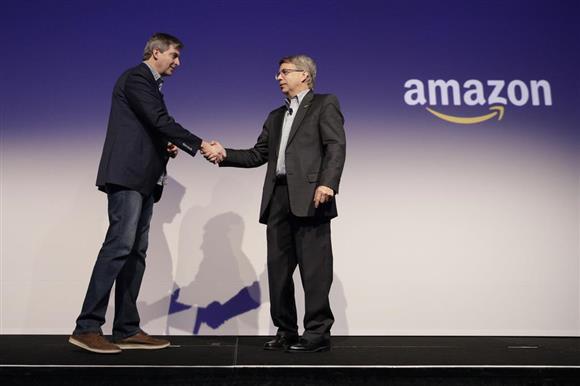記者会見後に握手を交わすアマゾンのトム・テイラー副社長(左)と北米パナソニックのトム・ゲッパートCEO=8日、米ネバダ州ラスベガスのCES国際会場(AP)