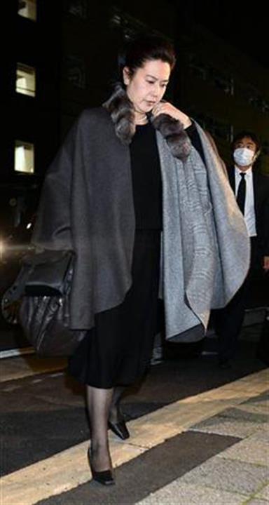 黒い服にロングコートを着て歩く名取裕子