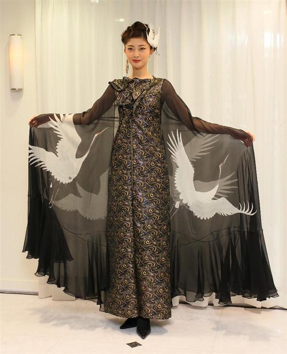 鶴の飾りを頭につけ鶴の模様があしらわれたマント姿の熊井友理奈