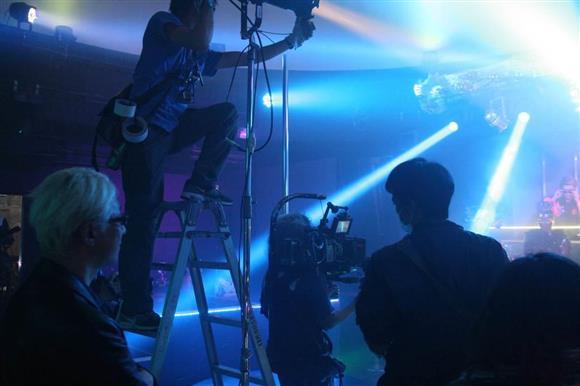 撮影風景。まばゆいライトが飛び交う中でクラブシーンの撮影が行われた。手前左が手塚眞監督=2015年12月21月、東京都渋谷区(藤井克郎撮影)