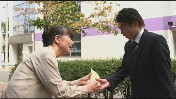 主人公の高校生がスーツを着て詐取金を受け取る啓発DVDのワンシーン