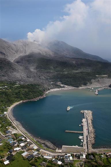 本村港に到着した「フェリー太陽」。奥には噴火した新岳が見えた=29日午後、鹿児島県の口永良部島(本社チャーターヘリから・鈴木健児撮影)