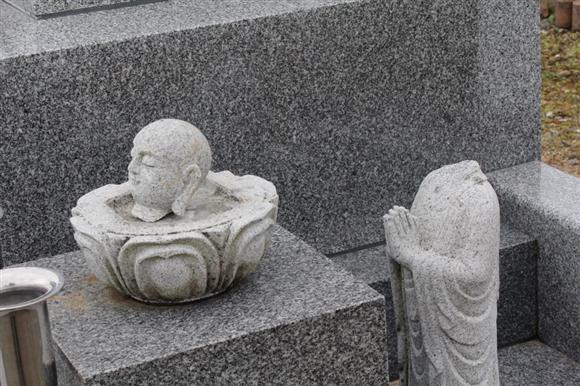 首を切断された地蔵像。首だけが蓮の上に置かれていた=福島県須賀川市柱田(三枝玄太郎撮影)