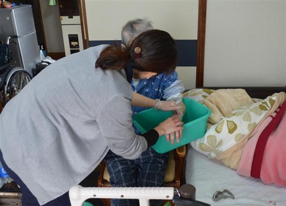 訪問先で利用者の腕をケアする訪問看護師=神戸市