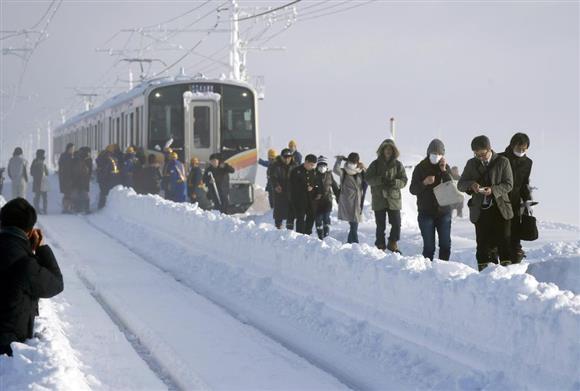 立ち往生したJR信越線の電車から降り、線路伝いに避難する乗客=12日午前8時13分、新潟県三条市