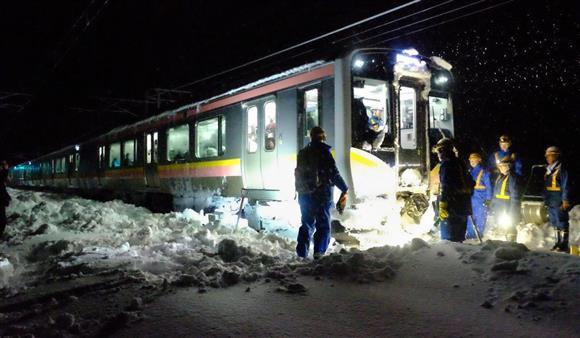 立ち往生したJR信越線の電車の周辺で、夜を徹して行われる除雪作業=12日午前1時35分ごろ、新潟県三条市