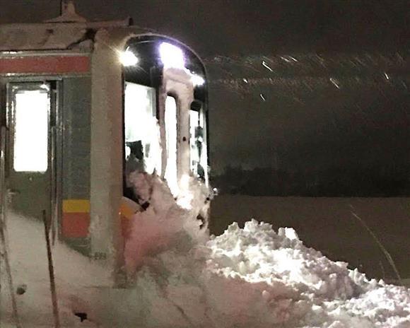 立ち往生したJR信越線の普通電車。先頭車両の前に雪が立ちはだかった=11日夜、三条市(同市の村岡志信さん提供)
