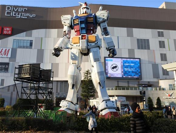 「RG1/1 RX78-2ガンダム Ver.GFT」とともに記念撮影する来場者=東京都江東区のダイバーシティ東京 プラザ2Fフェスティバル広場(撮影・津田克仁) (C)創通・サンライズ