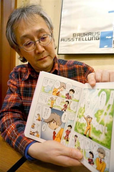 鬱病の経験者らの声をまとめた著書を手にする田中圭一さん=大阪市中央区