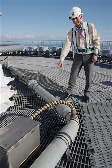 東京スカイツリーの高さ497メートル地点に設置された、雷の電流観測装置「ロゴスキーコイル」を指し示す研究者=平成29年7月31日、東京都墨田区(草下健夫撮影)