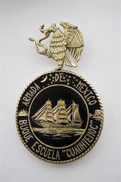クアウテモクのシンボルマーク。メキシコの国章である鷲と蛇のシンボルや、建造されたスペインからメキシコへのクアウテモクの航海の様子が描かれているという。