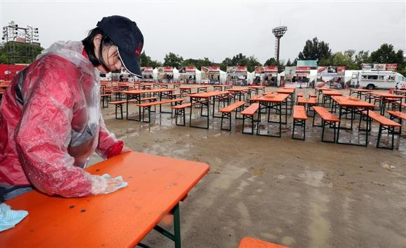 雨のなか開場の準備が進められる「肉フェスOSAKA」=16日、大阪市東住吉区の長居公園(門井聡撮影)