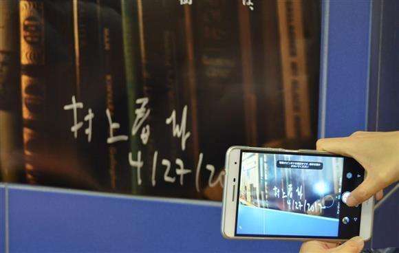 多くの人でにぎわった村上春樹さんのトークイベント。ポスターに書かれた村上さん直筆のサインを撮影するファンも大勢いた=2017年4月27日、東京都内(海老沢類撮影)