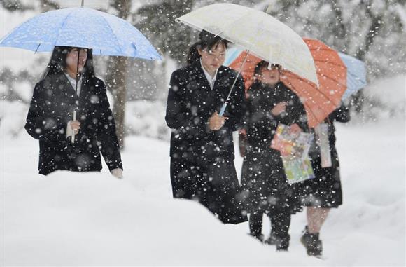 大雪の中、大学入試センター試験の会場に向かう受験生=13日午前、福井市の福井大学(永田直也撮影)