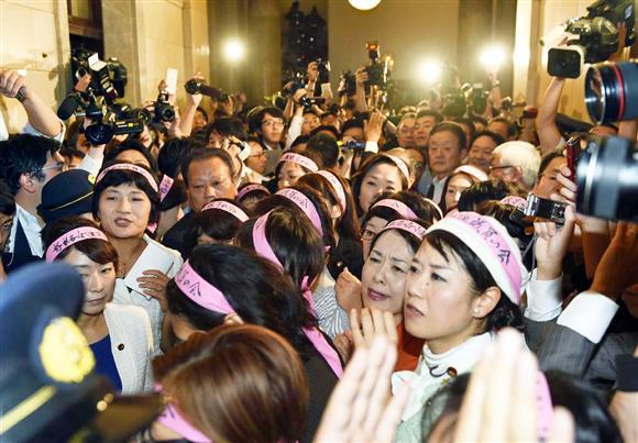 「怒れる女性議員の会」と記されたピンク色のはちまきを巻いて参院第一理事会室前に集まった議員=16日夕