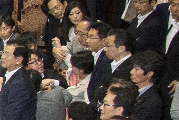 自民党の大沼瑞穂参院議員(写真中央白のスーツ)に手をかける民主党の津田弥太郎参院議員(写真中央、大沼氏の真上のグレーのスーツ)。大沼氏はこの後、写真右手奥までひきずられ、膝の上に乗せられた後に引き倒された=9月17日、参院第1委員会室(大沼事務所提供)