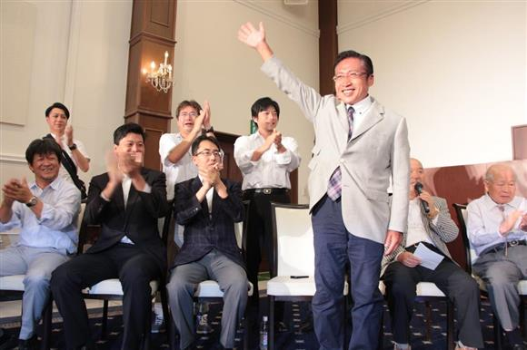 「当確」の情報に、拍手で祝福する支持者に手を挙げて応える渡辺喜美氏=7月10日、栃木県大田原市