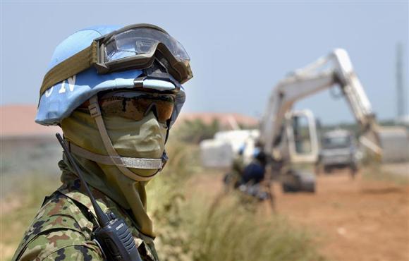 南スーダン・ジュバの道路整備作業で、辺りを警戒する陸上自衛隊員=2015年7月(共同)