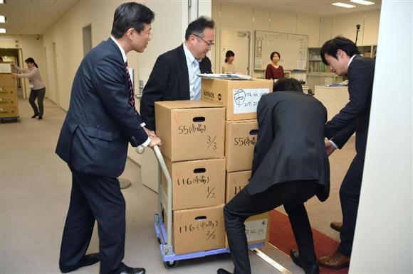 都議会の各会派に配布するため、要求資料が入った段ボール箱を運ぶ関係者=9日午後、都庁