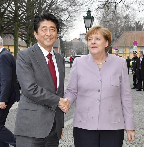 会談を前に握手を交わすドイツのメルケル首相(右)と安倍首相=20日、ドイツ・ハノーバー(代表撮影・共同)