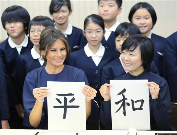 11月6日、京橋築地小学校の授業を見学し、毛筆した「平和」の文字を見せるメラニア米大統領夫人(手前左)と安倍昭恵首相夫人(同右)=東京都中央区(代表撮影)