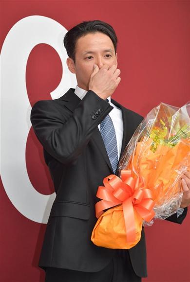 球団職員から花束を受け取った松本は感極まって涙を流し、鼻に手をやった (撮影・戸加里真司)