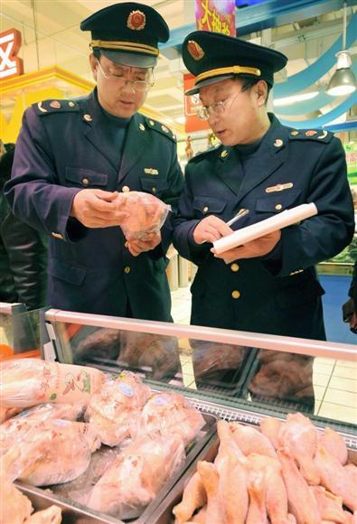 鶏問題でスーパーで鶏肉を調べる中国当局=2012年12月(共同)