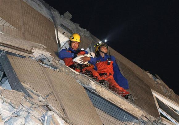 6日、台湾南部の台南市で、地震により倒壊したビルから布に包まれた赤ちゃんを運び出すレスキュー隊員(AP)
