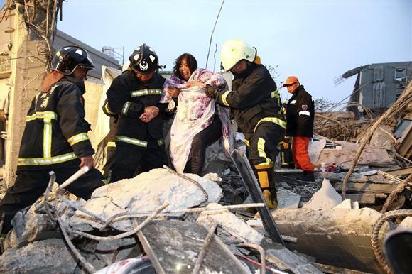 6日、台湾南部の台南市で、地震により倒壊したビルから救出される人(ロイター)