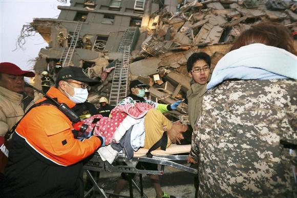 6日、台湾南部の台南市で地震により倒壊したビルから救出され、運ばれる男性(AP)