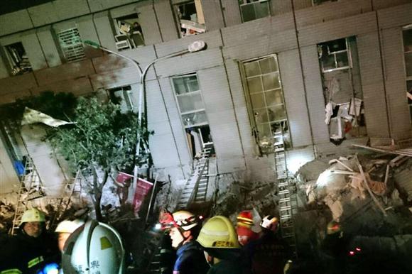 6日、台湾南部の台南市で、地震により倒壊したビル周辺で、住民らの救出作業に当たる消防隊員ら(中央通信社=共同)