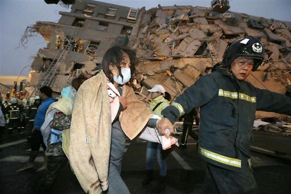 地震で倒壊したビルから救出された女性=6日、台湾南部の台南市(新華社=共同)
