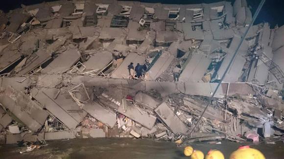 台湾の地震で倒壊したオフィスビルで救出活動を行う人たち=6日(AP)