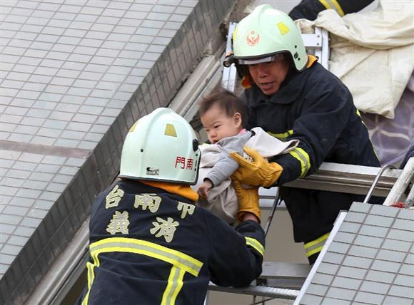 6日、台湾・台南市の17階建て集合住宅の倒壊現場から助け出される赤ちゃん(ロイター)