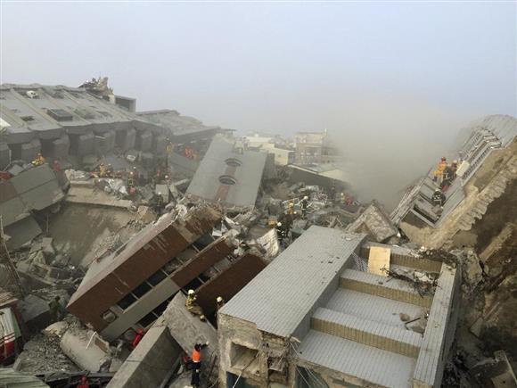 6日、地震により倒壊した17階建ての集合住宅=台湾・台南市(ロイター)
