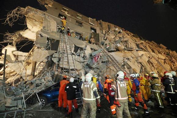 地震により倒壊したビルで救助活動するレスキュー隊員ら=6日、台湾南部の台南市(新華社=共同)