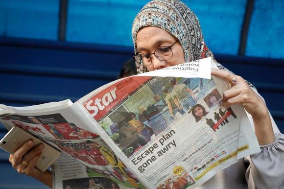 金正男氏暗殺をトップで報じる新聞を病院の待合室で読む女性=17日、クアラルンプール(AP)