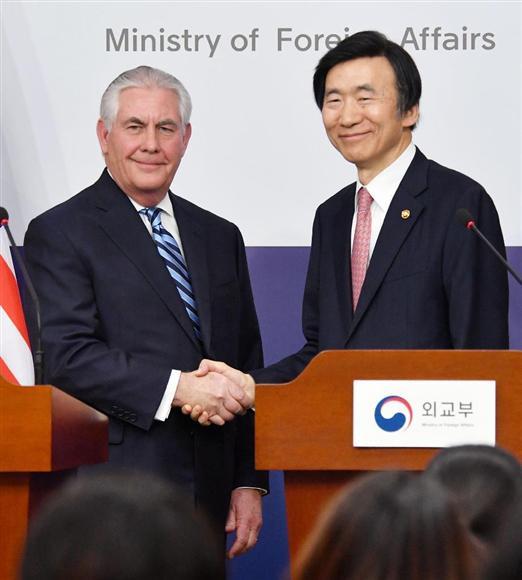 17日、共同記者会見を終えティラーソン米国務長官(左)と握手する韓国の尹炳世外相=ソウルの韓国外務省(共同)