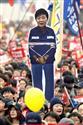 囚人服姿の朴槿恵大統領のパネルを手に、韓国大統領府の近くで抗議する人たち=2016年12月、ソウル(共同)