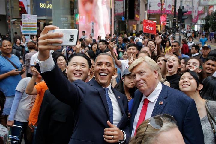 仲良く自撮りする(左から)金正恩・朝鮮労働党委員長、バラク・オバマ米前大統領、ドナルド・トランプ米大統領のそっくりさん=7日、香港(AP)