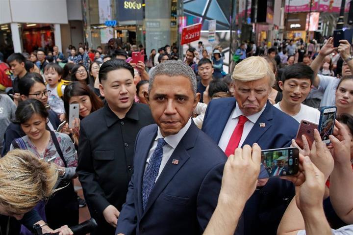 沿道を埋めたファンの撮影に応じる(左から)北朝鮮の金正恩・朝鮮労働党委員長、バラク・オバマ米前大統領、ドナルド・トランプ米大統領のそっくりさん=7日、香港(AP)